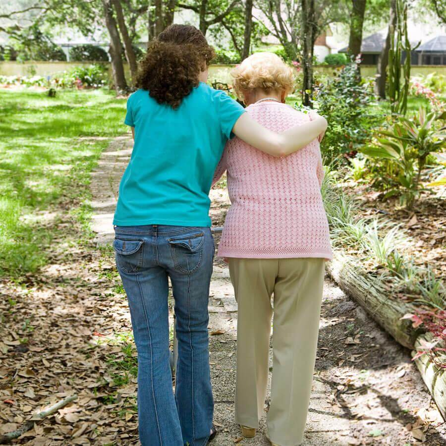 Caregiver helping an old woman walk
