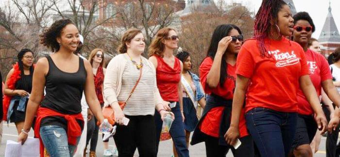 Women marching while wearing red