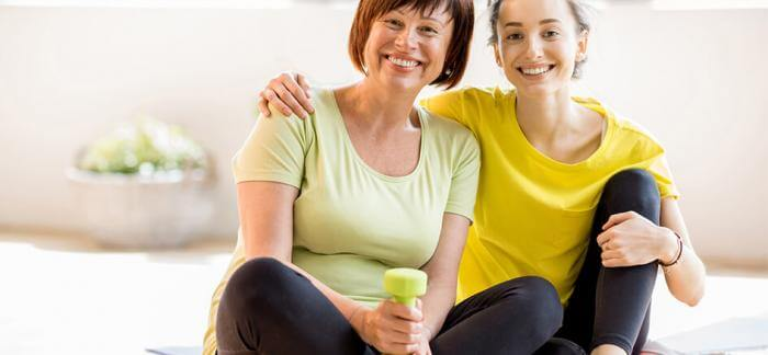 Two women seated on a fitness mat