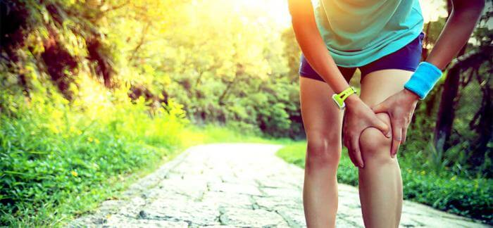 Runner gripping knee on running trail