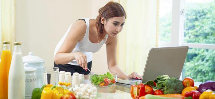Woman eating a salad and using her laptop