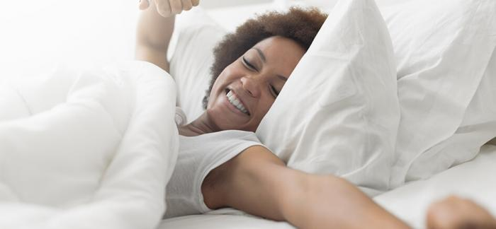 Mujer estirando los brazos después de una noche de descanso