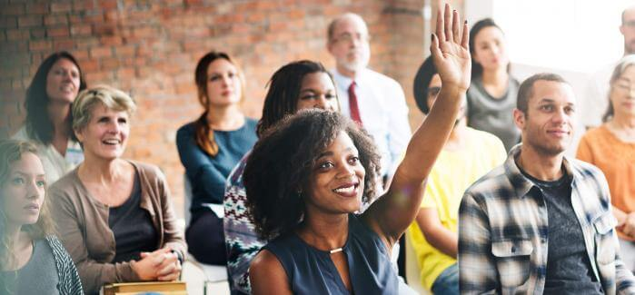 Woman raising hand in group meeting
