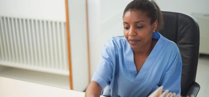 Woman in medical scrubs working at a laptop