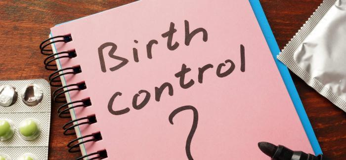 "A condom, birth control pills, and a notepad with ""Birth control?"" written on front."