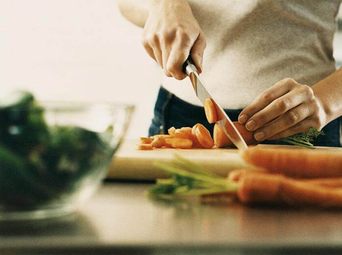 A person cutting carrots for a healthy meal