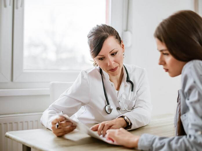 Health professional and patient reviewing medical paperwork