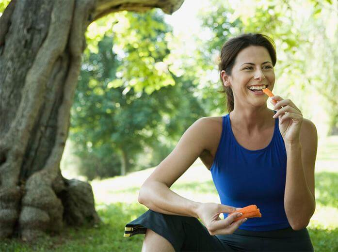 A woman enjoying a healthy snack outdoors
