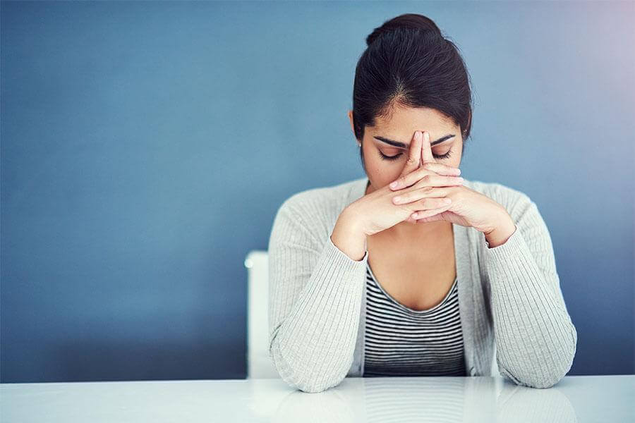Stressed woman with her hands covering her face