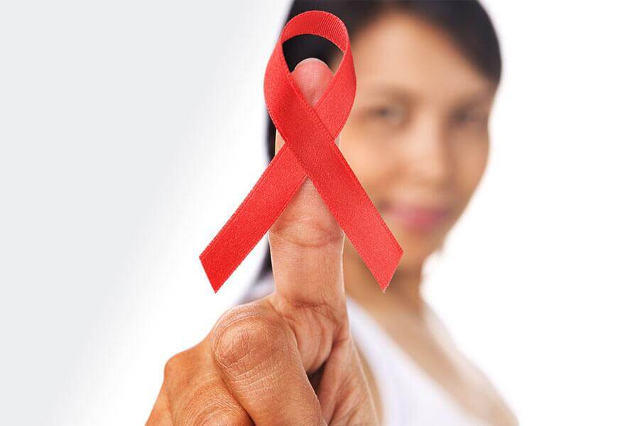 Woman holding red HIV/AIDS awareness ribbon.