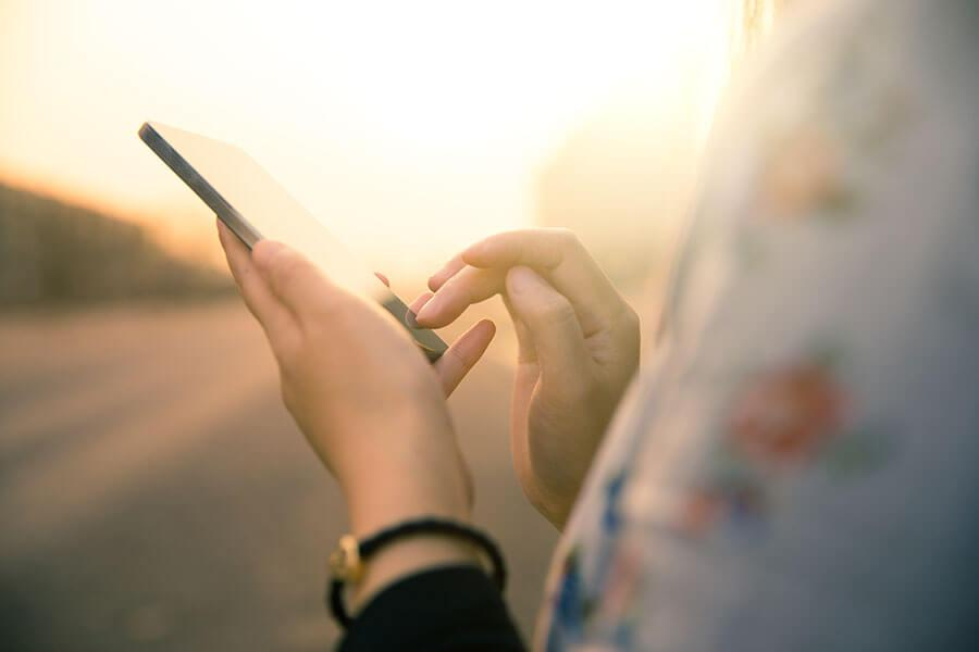 Image of a woman holding a smartphone.