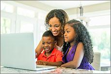 A mother and two children on a laptop
