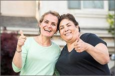 Two women making a thumbs-up gesture